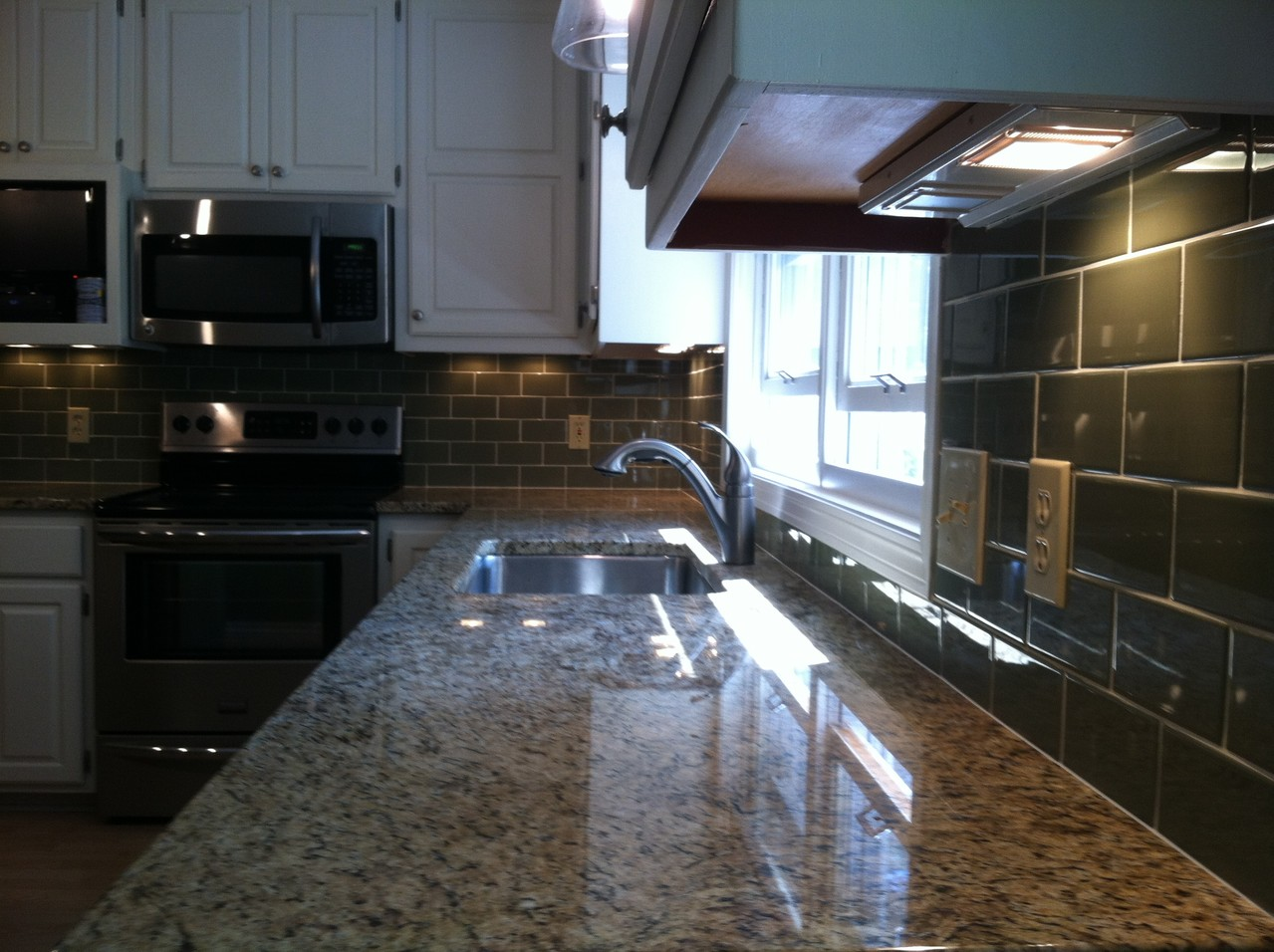New granite countertops with ceramic tile backsplash