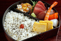 a lunch box fresh slices of raw fish