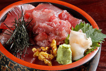 a bowl of rice topped with slices of raw tunas