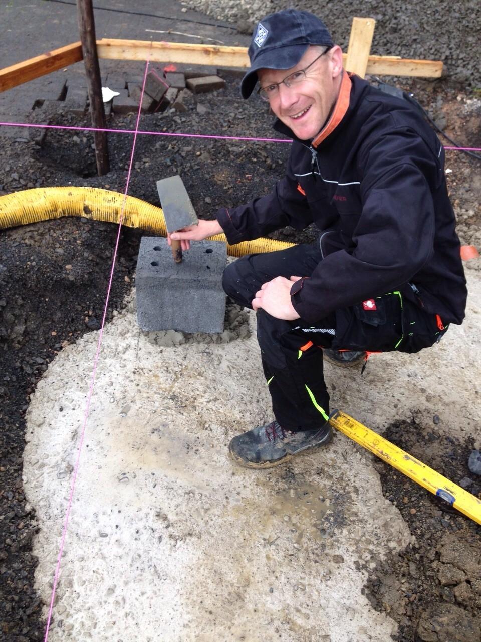 Bauleiter Dirk setzt den ersten Stein