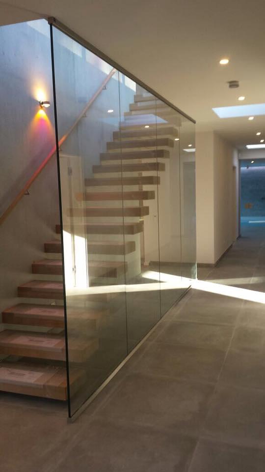 Brüstung seitlich einer Treppe mit einem dezenten Profil an der Decke und auf dem Boden. Verbaut wurde 17mm dickes Vebundsicherheitsglas.