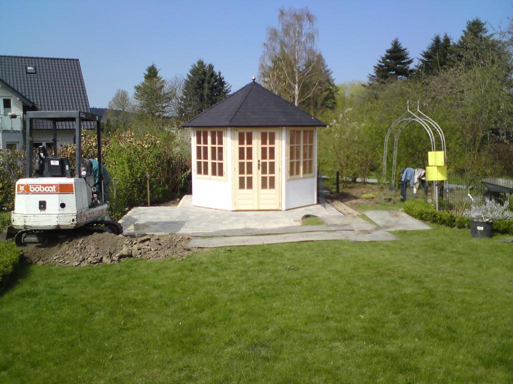 Korfmacher Gartengestaltung setzt das Pavillon-Gartenhaus auf seinen Platz.