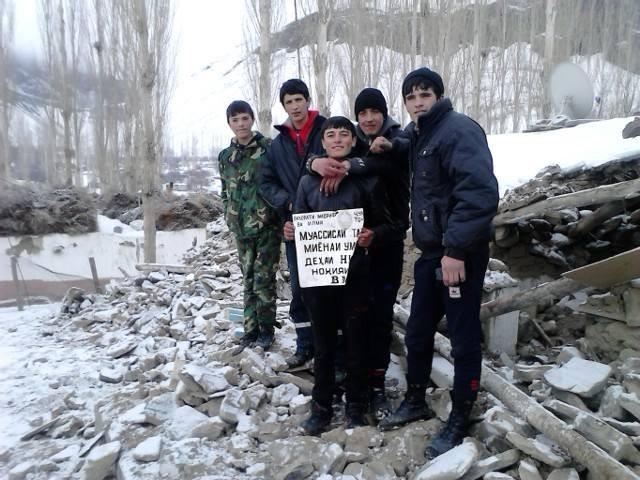 Schüler aus Nisur mit dem Schild ihrer völlig zerstörten Schule.