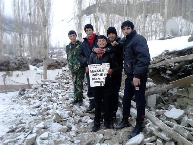 Students of Nisur with the former sign of their completely destroyed school building. Earthquake, Pamir, Bartang, Tajikistan, Gorno-Badakhshan, GBAO