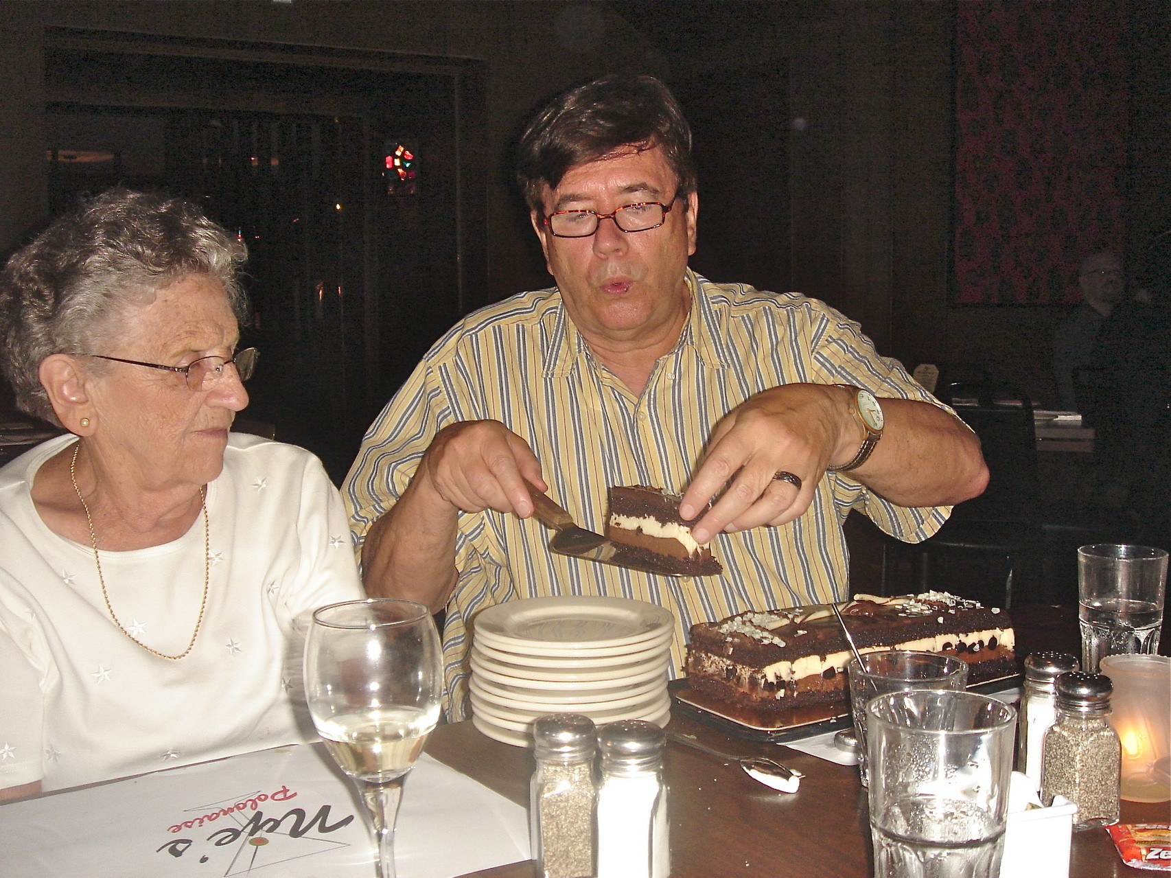 John cuts the cake as Mary Lou looks on.
