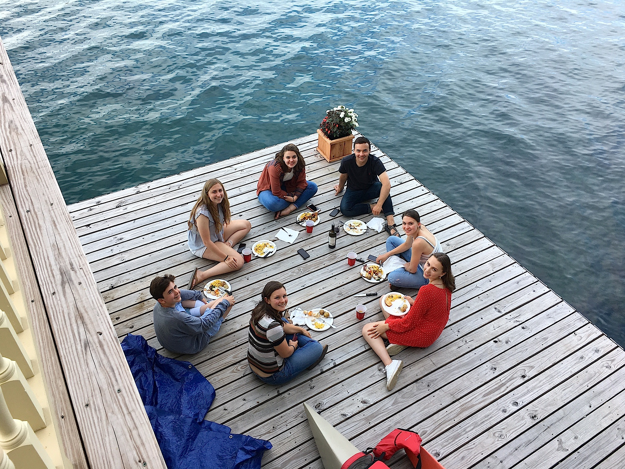The teens eat dinner on the dock