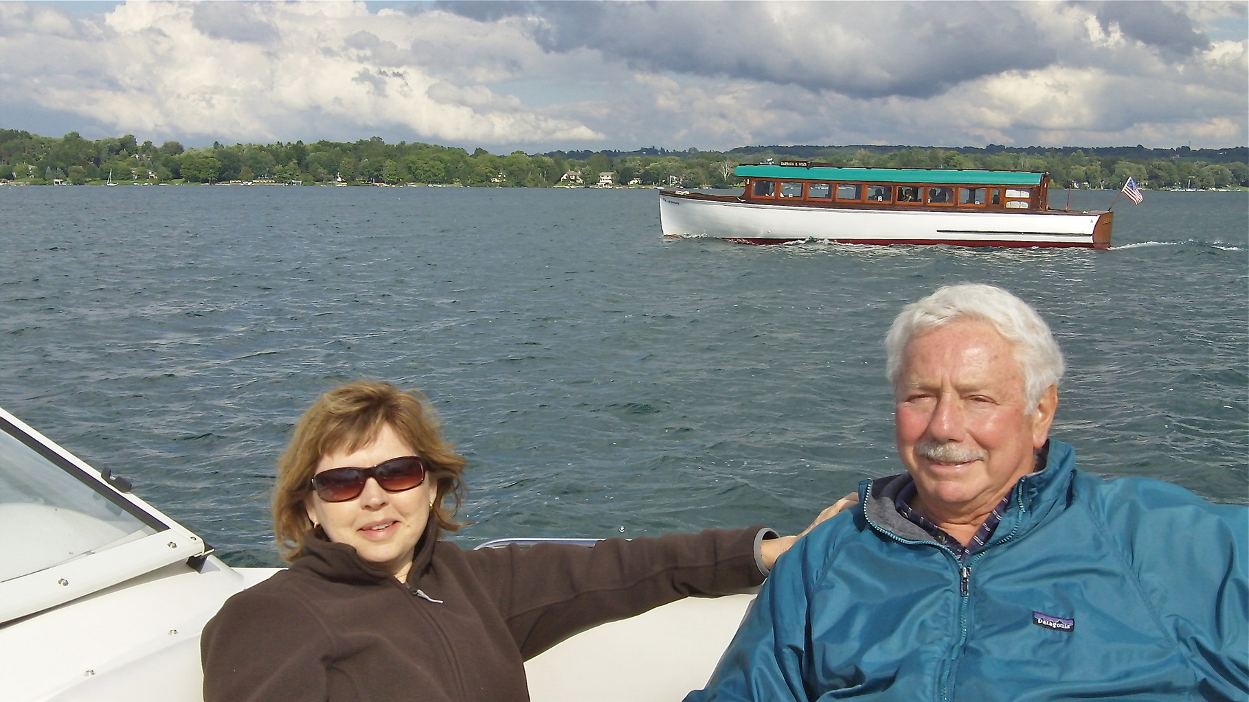 Barbara & Don, mailboat in the background, Skaneateles Lake