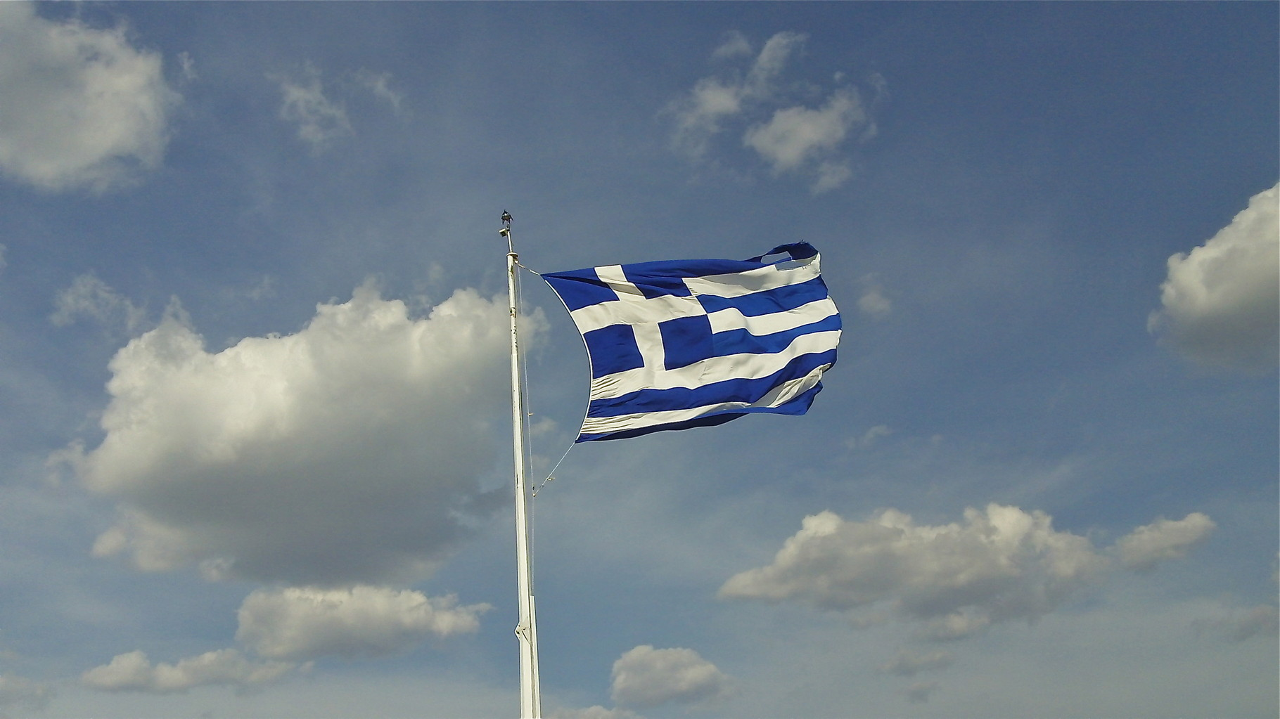 the Greek flag waves in the breeze at the Acropolis