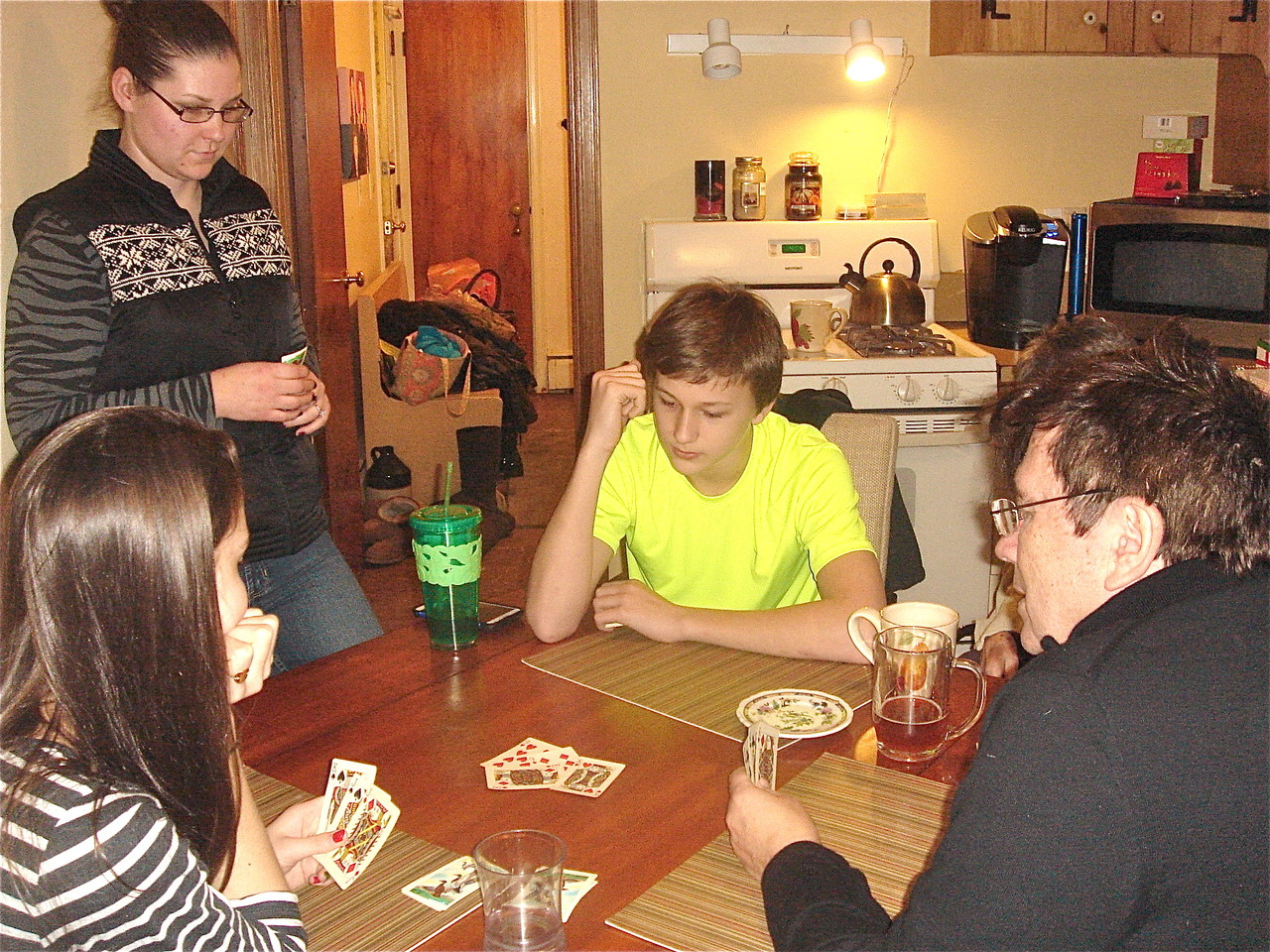 Ellie, caregiver Jesika, Jack Kagel learn Euchre from John Wagner