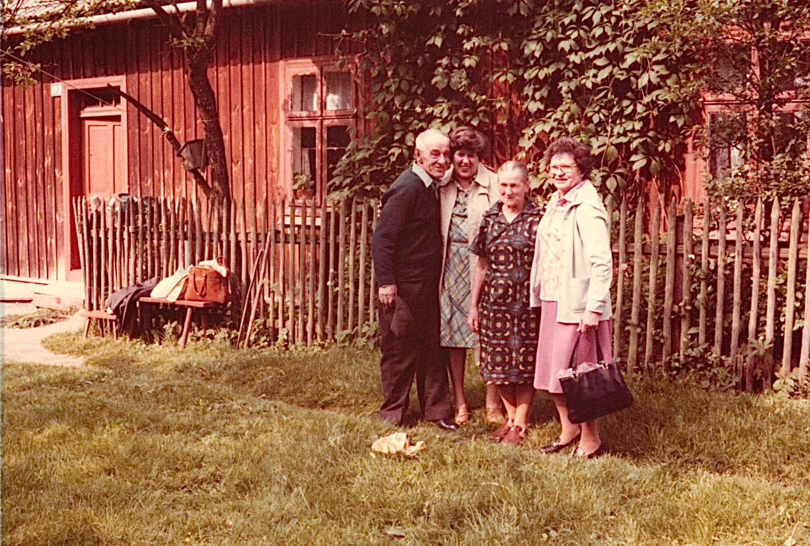 Walter, Eleanor, Julia, & Mayme.  Walter is Eleanor & Mayme's uncle.  Two months before we arrived Walter received a transistor radio as a present. House has no electricity or heat, just a stove. Note the fir to wipe your feet at the door.