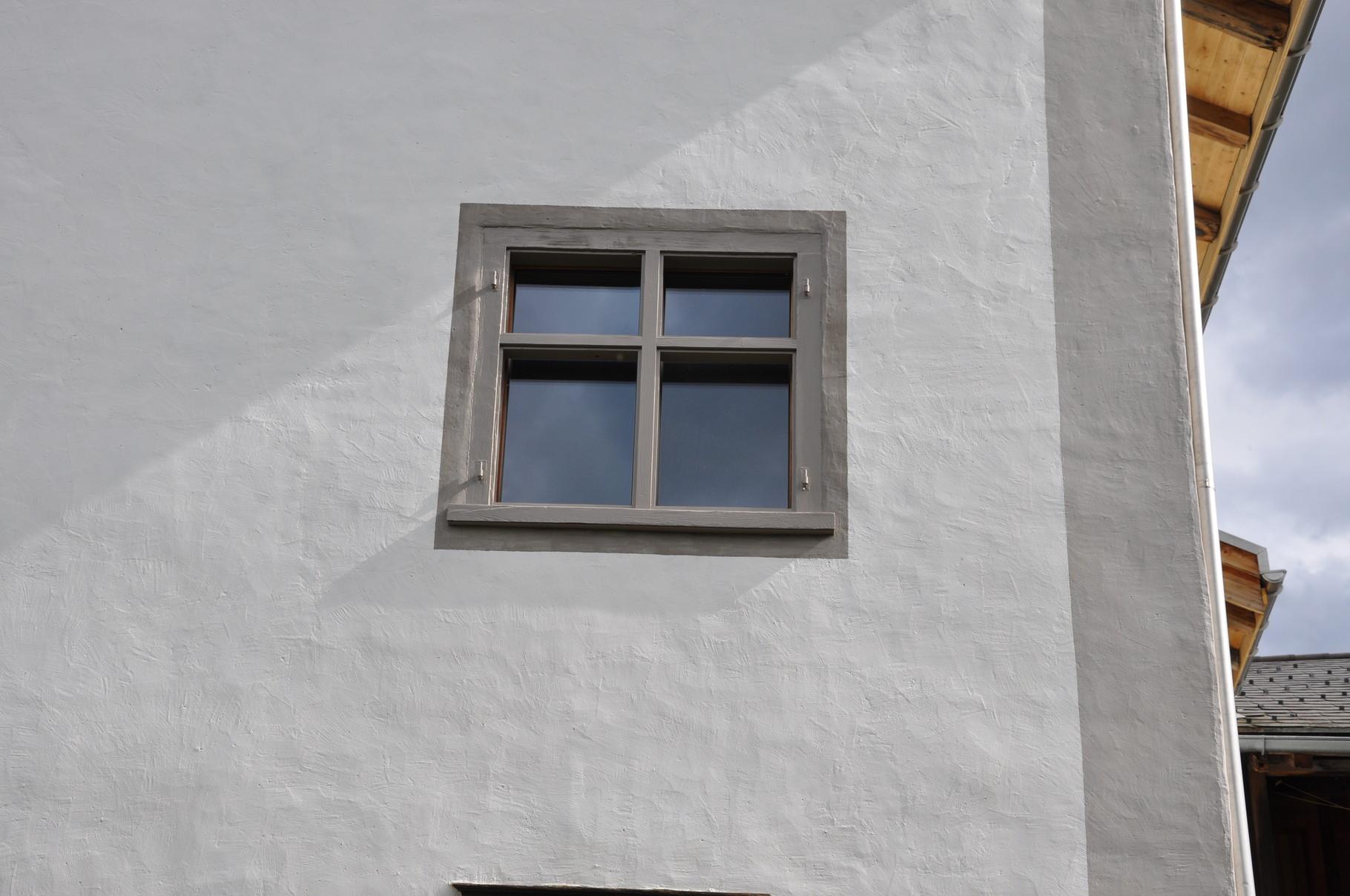 Detail Kalkputz mit aufgemalten Ecklisenen und Fenstereinrahmungen in versch. Grautönen