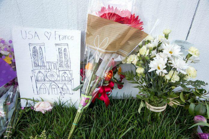 زهور وبطاقات ترمز لمشاعر التعاطف وُضعت عند أبواب سفارة فرنسا في واشنطن في اليوم التالي للحريق الذي شبّ في كاتدرائية نوتردام. (State Dept./D.A. Peterson)