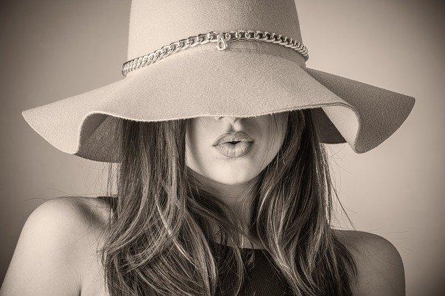 cette photo en noir et blanc représente une femme avec un chapeau sur les yeux et des cheveux longs.
