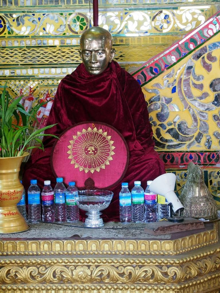 An Buddha und Mönchsfiguren werden Spenden aller Art abgelegt