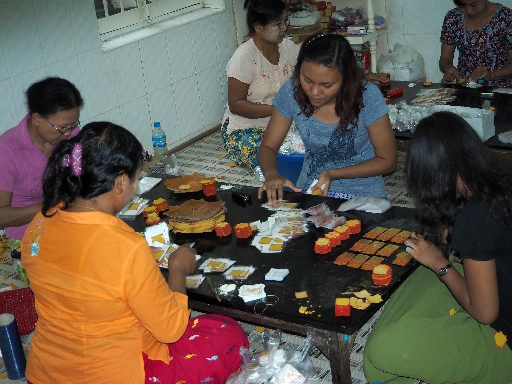 Frauen verpacken das Blattgold zu verkaufsfähigen Einheiten
