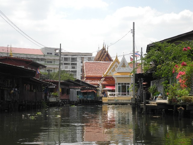 Gegensatz - mondäner Buddhatempel neben armen Khlongpfahlbauten