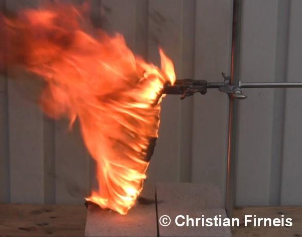 Ein Nitrilhandschuh reagiert mit rauchender Salpetersäure unter Feuererscheinung