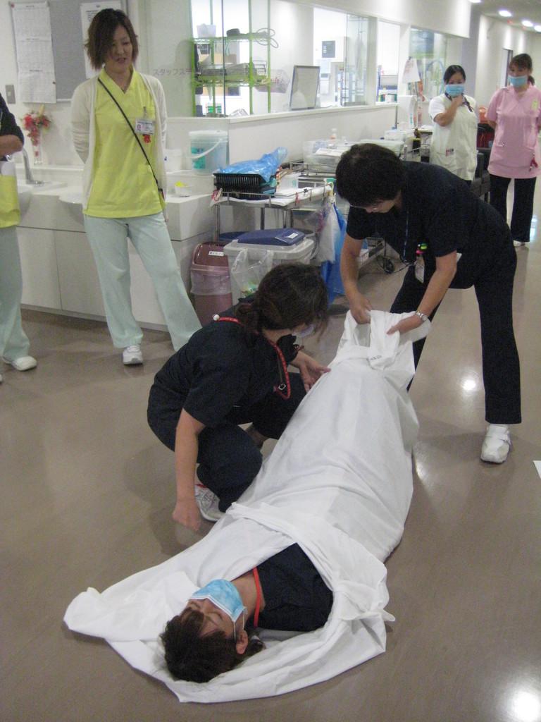 患者さんをシーツでくるみ、移動します
