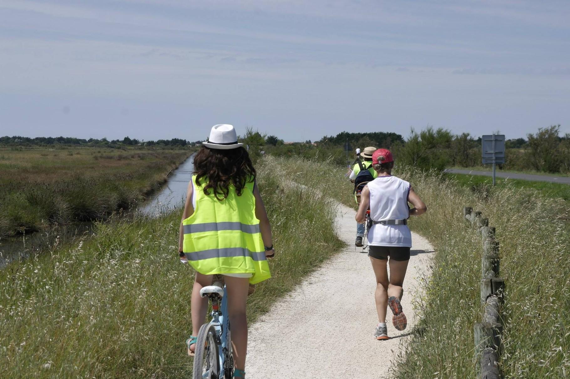 Sur leur vélo, les bénévoles fournissent en continu les coureurs en eau, céréales et bananes