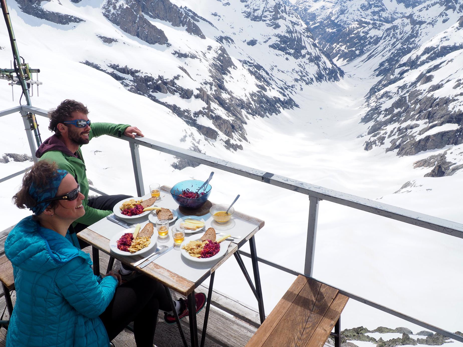 Seuls au soleil devant des montagnes enneigées, le déjeuner de l'équipe du refuge