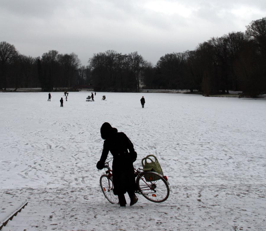 Frau mit Fahrrad betritt die Eisfläche des Karpfenteichs im Schlossgarten Charlottenburg. Foto: Helga Karl
