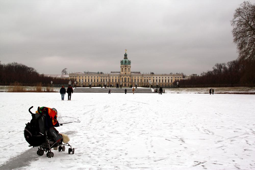 Menschen auf dem mit Schnee bedeckten gefrorenen Karpfenteich mit Blick auf Schloss Charlottenburg. Foto: Helga Karl