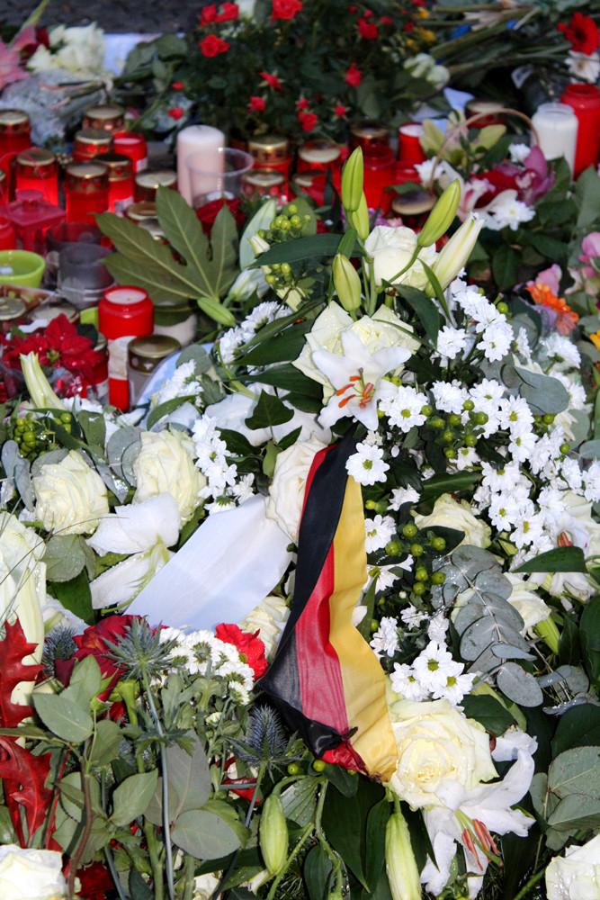 Ein Deutschland-Fähnchen inmitten von Blumen und Kerzen nach dem Terror-Anschlag in Paris. Foto: Helga Karl