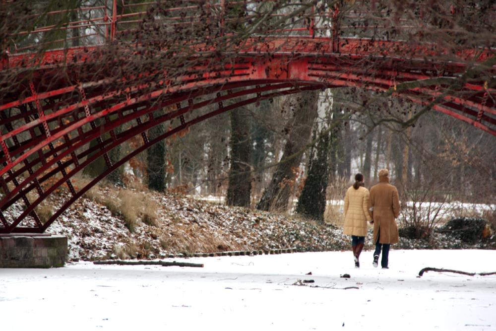 Menschen gehen auf dem schnee-bedeckten Eis unter der Roten Brücke im Schlossgarten Charlottenburg. Foto: Helga Karl Januar 2009