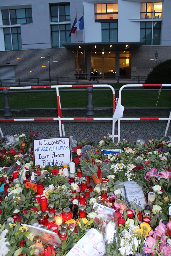 """""""In Solidarität"""". Schild inmitten Blumen und Kerzen vor der französischen Botschaft in Berlin nach IS-Terror in Paris. Foto: Helga Karl"""