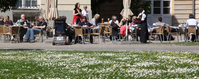 Im Freien sitzende Gäste. Cafe vor dem Schloss Charlottenburg, davor ein Rasen mit weißen Gänseblümchen. Foto: Helga Karl