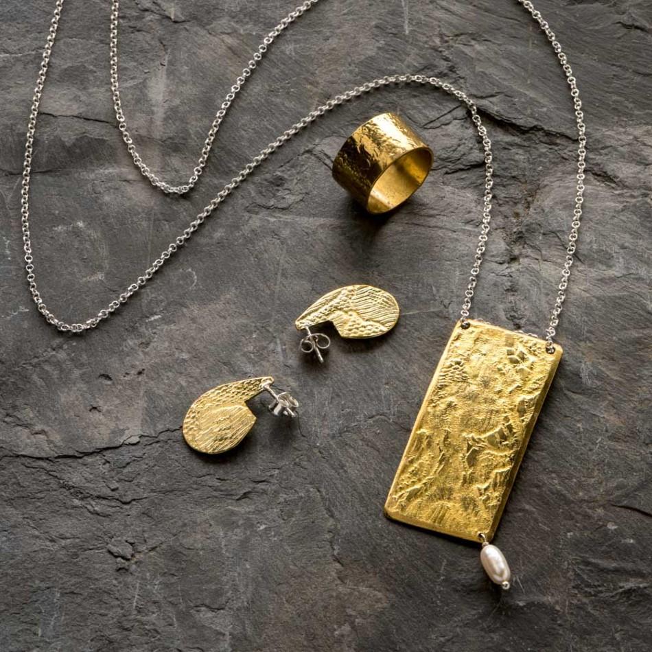 Parure empreinte dentelle couleur or, le collier est long et pendentif a une perle de culture,  les créoles ont un système de fermeture en argent