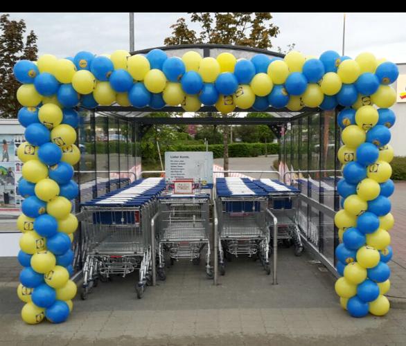 Ballongirlande mit mittigem Pfeil über der Einkaufswagenbox. LIDL.