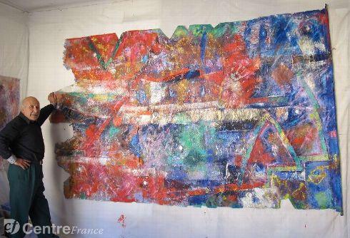 Moussa Tiba staat links van een heel groot schilderij, geschilderd op linnen, de kleuren rood-oranje, goud en blauw overheersen.
