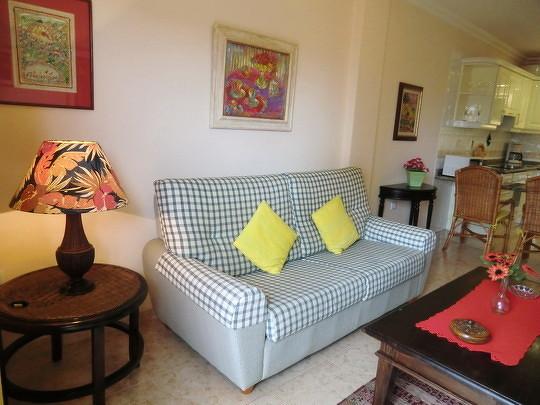 Bild: Es zeigt das Sofa im Wohnbereich mit einer Leselampe, im Hintergrund ist die offene helle Küche zu sehen.