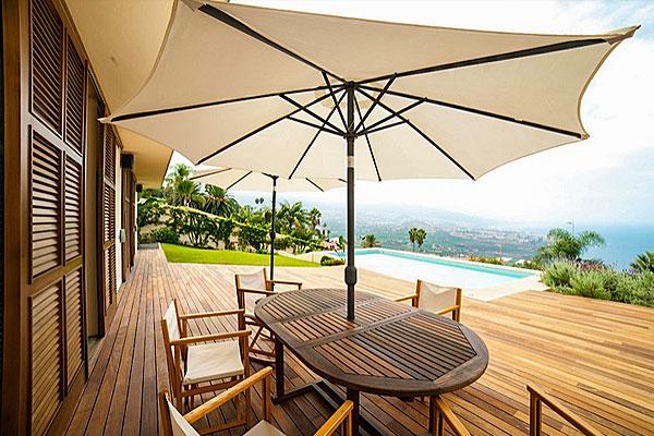 Holzterrasse mit Gartenmöbel, Pool im Hintergrund und einmaliger Meerblick.