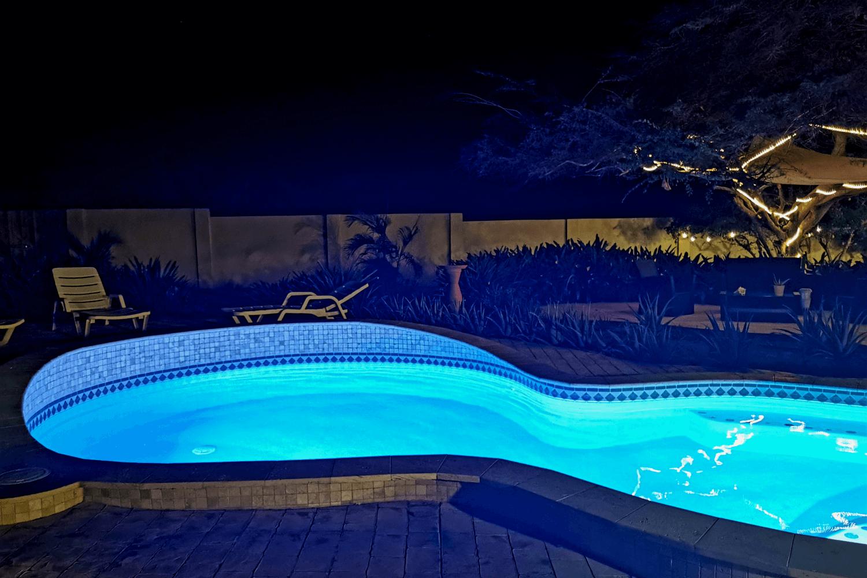 Nachts ist der Pool beleuchtet und lädt zu einer Runde schwimmen unterm Sternenhimmel ein