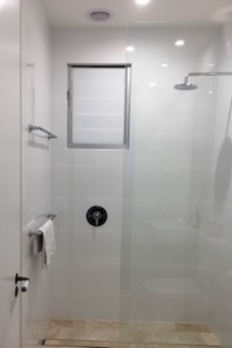 Shower with glass doors, round silver shower head (UK), lever shower mixer (UK), silver towel rack