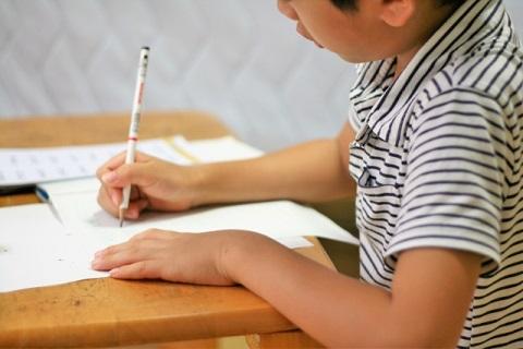 机に向かって学校の勉強している小学生の男の子