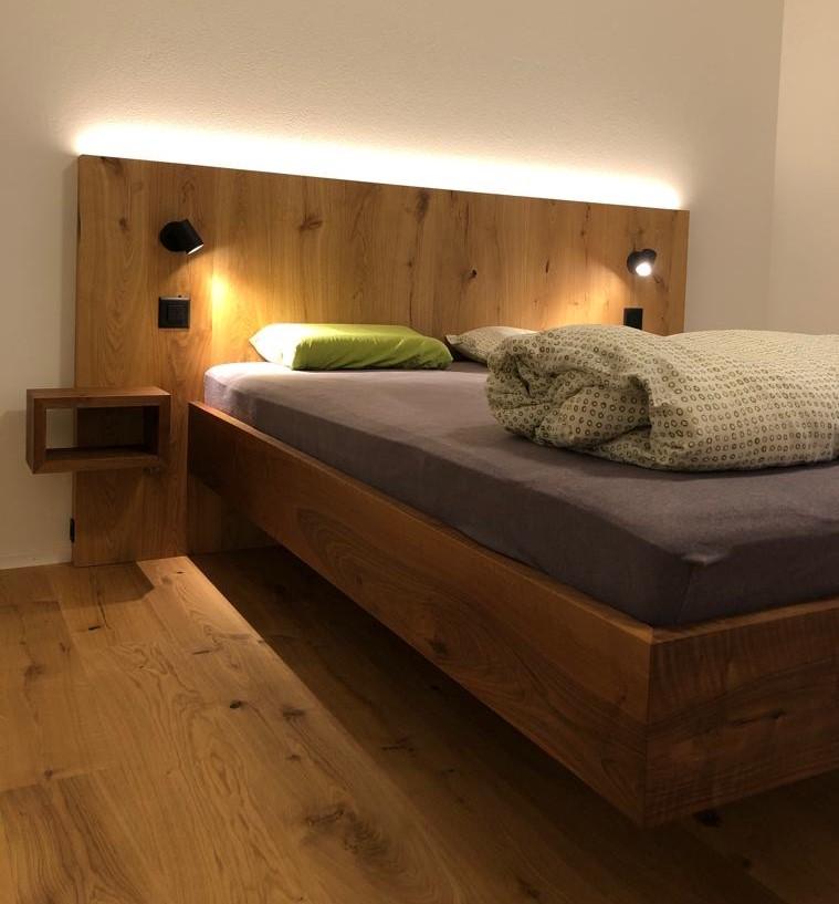 Nussbaum Bett, Kopfteil mit Parkett fliessend hochgezogen, passende Ablagen sowie integrierte Lichtquellen