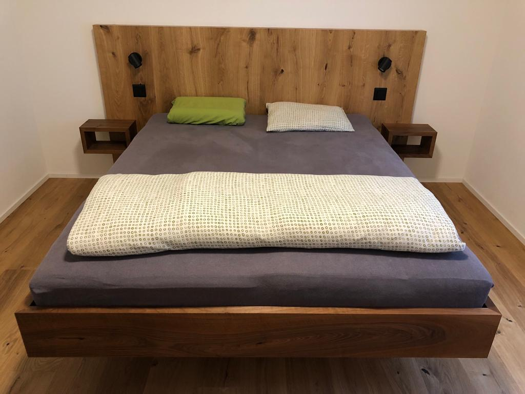 Bett Nussbaum, Kopfteil mit Parkett fliessend hochgezogen, passende Ablagen sowie integrierte Lichtquellen