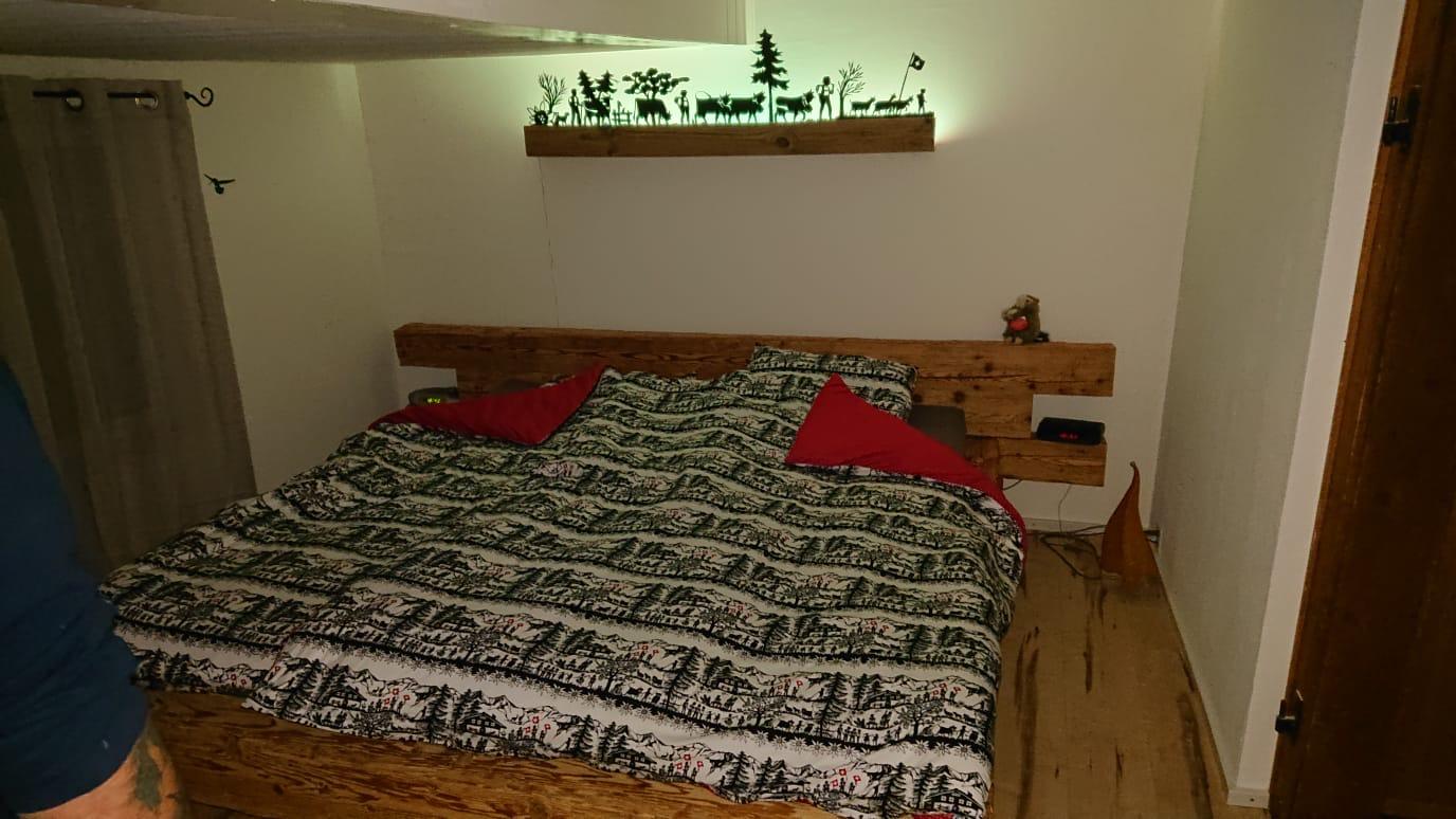 Lungerer Altholz Balken Bett mit Schaf Wolle Kissen