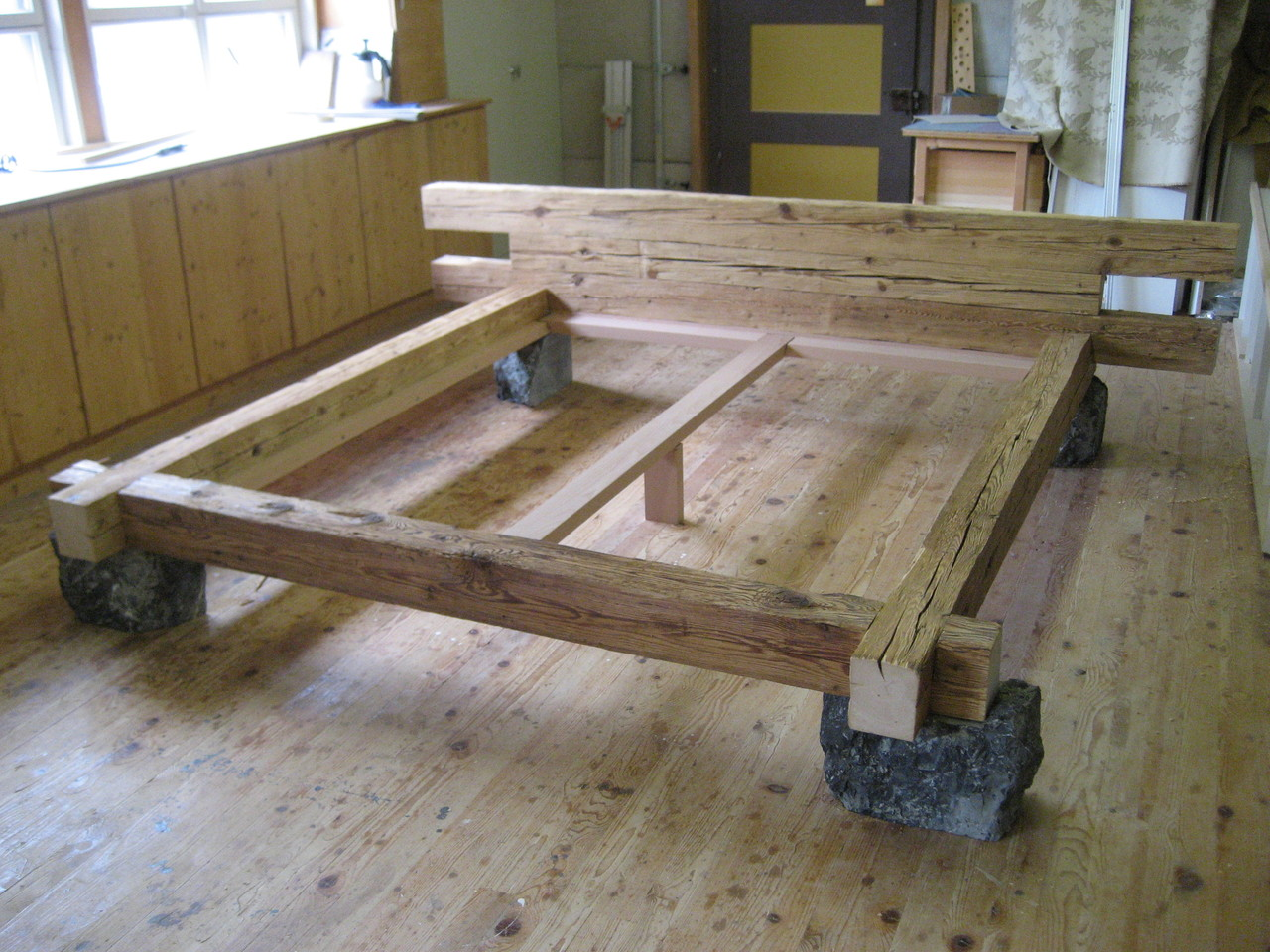 Bett in Altholz mit Natursteinbein