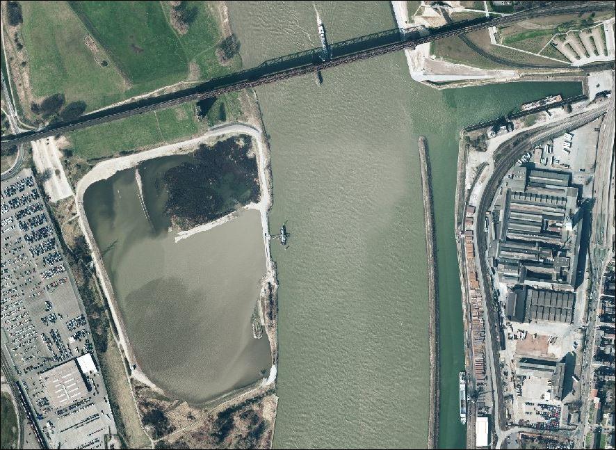 """Quelle: """"Regionalverband, Ruhr CC BY-NC-SA 4.0"""" Das Luftbild zeigt die Auskiesungsarbeiten in der Rheinaue im Jahr 1995. Links im Bild eine Logport-Lagerfläche für Autos. Deutlich erkennbar auch die Hafenmole des Südhafen."""