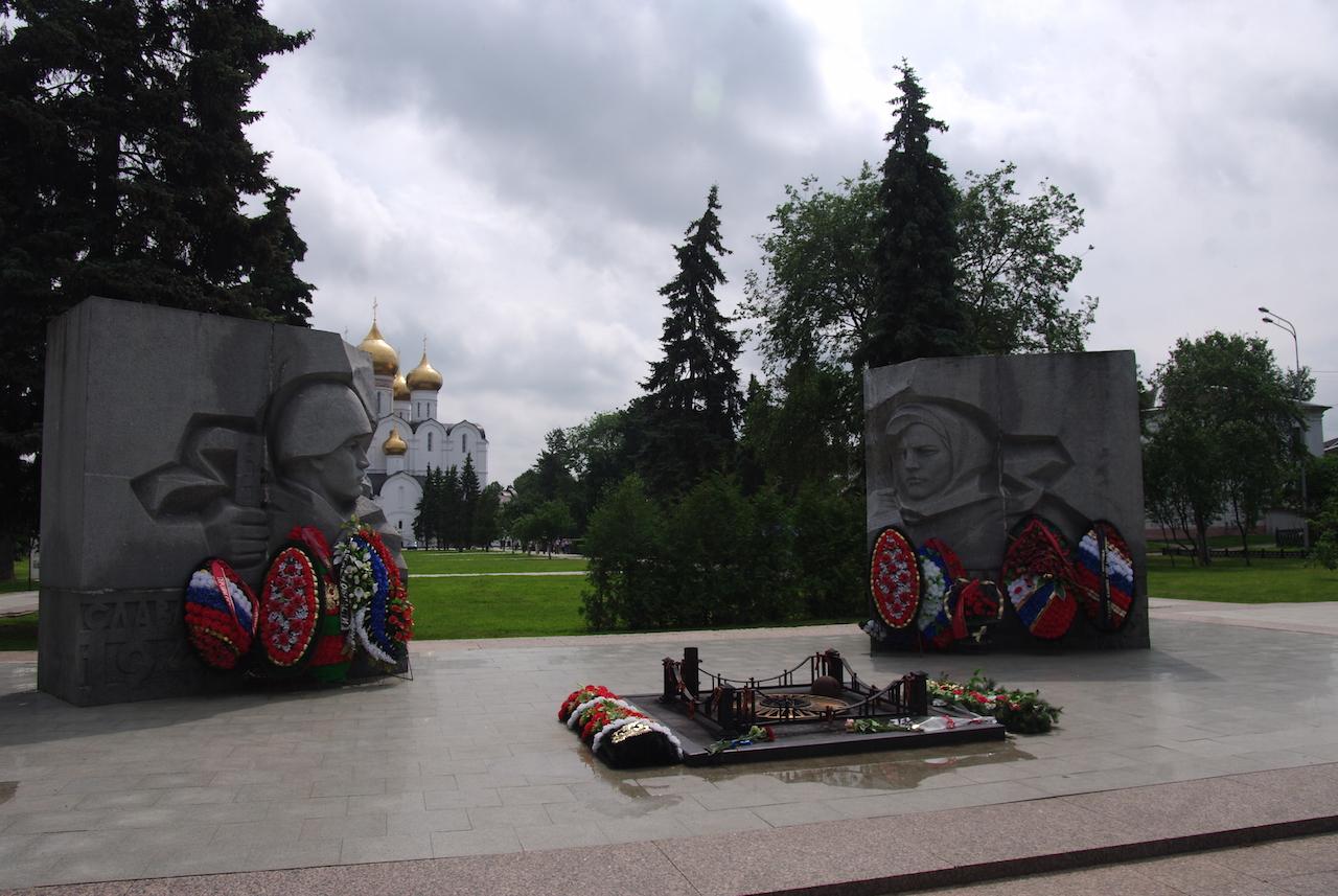 Le monument aux morts, ses fleurs artificielles, au fond : la cathédrale.