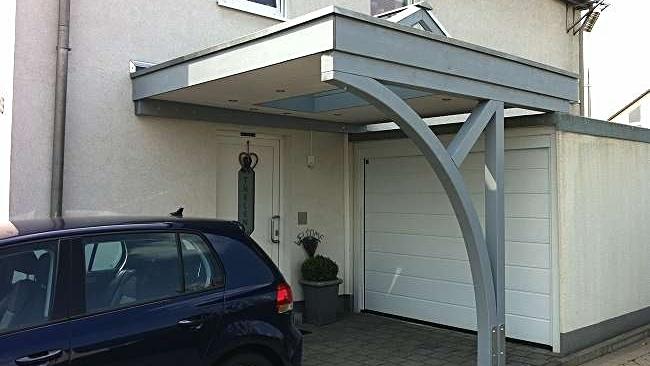 Beispiel Nr. SOC10   Kleine Carportanlage mit Glasaufsatz vor einer Garage. Mit MONZA Bogenpfosten. Gleichzeitige Überdachung des Hauseinganges.