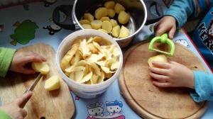 Ein 3jähriger und ein 5jähriger bereiten Kartoffeln vor.