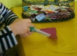 Das selbe Kind übt sich mit der Plastikschere.
