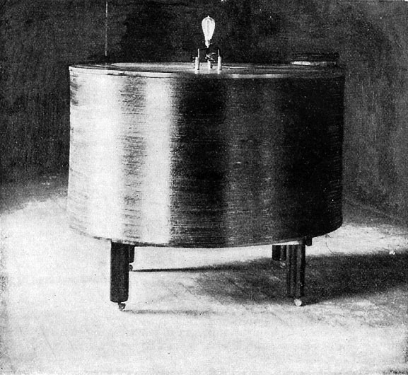 Fig. 10. — Experiment showing the lighting up of an ordinary incandescent lamp, at a distance, through the influence of electrified ether-waves. (From flash-light photograph.)