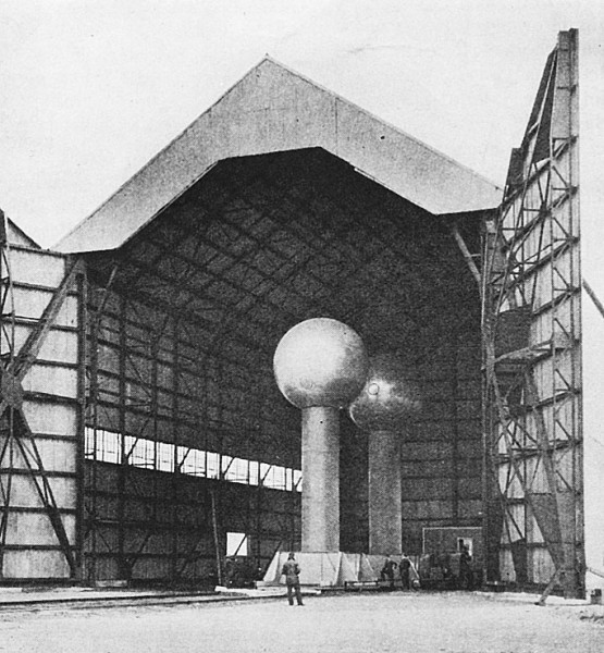 The Van de Graaff generator, shown housed in an aircraft hangar, is discussed by Dr. Tesla in the accompanying article.