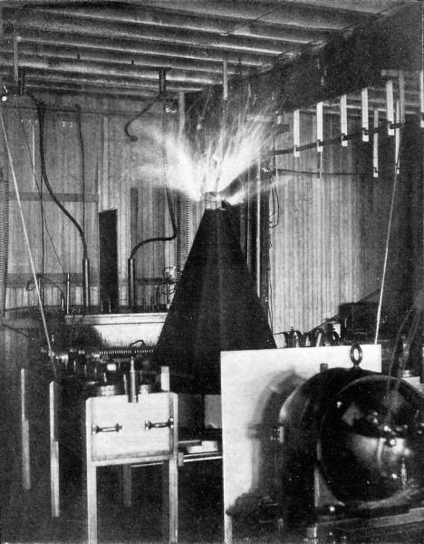 Fig. 15. — Tesla Coil for ascertaining and discharging the electricity of the earth. The streamers at top of coil are of purple hue, and in form resemble filaments of seaweed, the effect of mass being caused by prolonged exposure of flash-light negative.